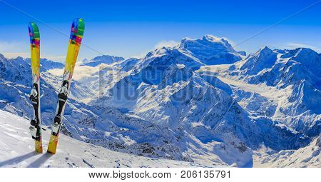 Skiing in winter season, mountains and ski equipments on the top of snowy mountains in sunny day. Swiss Alps.
