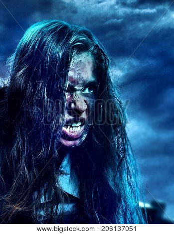 Undead zombie scary girl on halloween graveyard at night on dark clouds sky background. Dangers woman in zombie apocalypse go out hunting outdoor. Toned close up of monster face on clouds background.