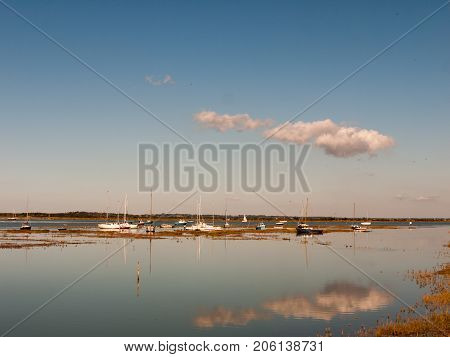 Beautiful Estuary Scene With Blue Sky Moored Boats, Masts, And Reflection Of Cloud In Water Surface