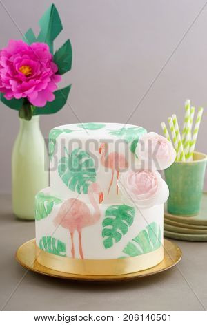 Two tiered tropical wedding cake with fondant, tropical wafer paper leaves and flamingos with ranunculus flowers on golden cale platter poster