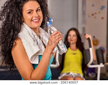 Woman in gym workout with fitness equipment. Girl drink from bottle water relaxing after workout at gym. Maintain a good physical shape. She has sport towel around his neck.