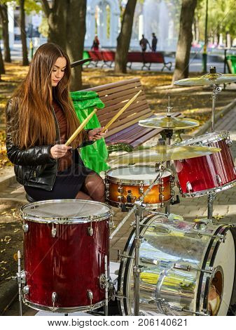 Festival music band in autumn park. Sad woman playing on percussion instruments in city park. Girl is playing drums.