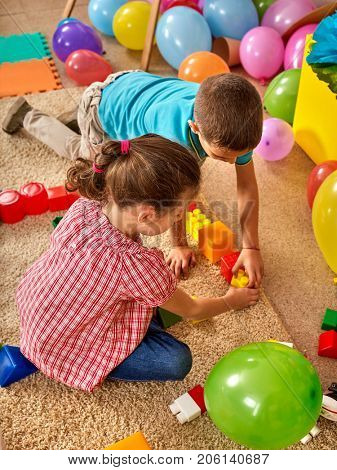 Children building blocks in kindergarten. Group kids playing toy on floor. Top view of interior preschool. Children develop their fingers in a game of cubes. Many balloons on floor.