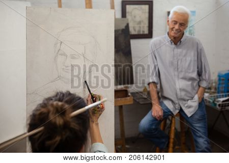 Senior man watching while artist drawing on canvas in drawing class