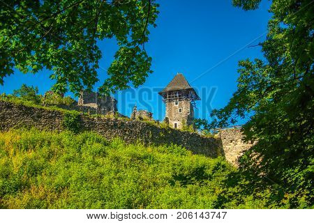 Castle tower and wall. Stone fortification on green hill on blue sky. Bastion on sunny summer day. Landmark and travel destination. Protection and defense concept