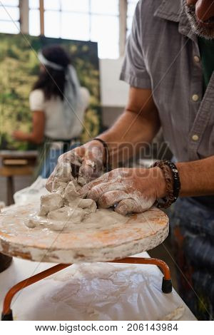 Mid section of man molding clay in class