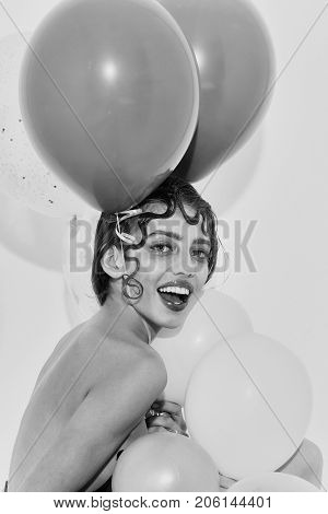 Pretty girl or cute woman with curly lock of hair hairstyle sexy rosy lips stylish makeup on happy face with party balloons colorful pink hearts has bare shoulder isolated on white background