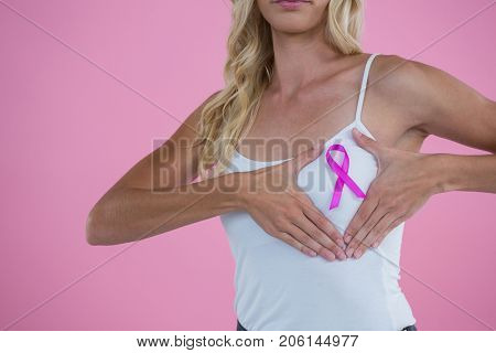 Mid section of woman showing Breast Cancer Awareness ribbon on breast against pink background