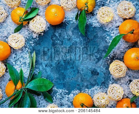 Farm fresh mandarin oranges fruit with leaves on rustic gray cloth background. Shallow focus