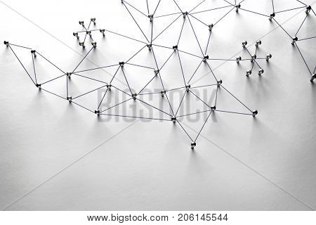 Linking entities. Monotone. Flat lay. Networking, social media, SNS, internet communication abstract. Small network connected to a larger network. Web of black wires of white background.
