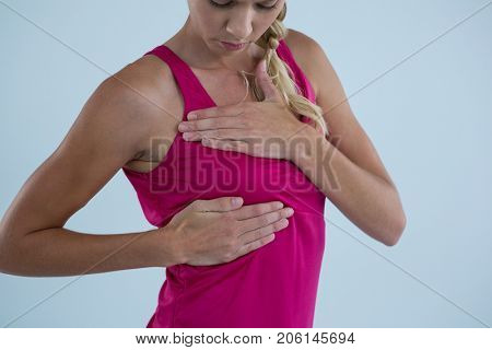Woman touching breast for lumps while standing against gray background