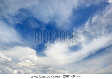 Heavenly seascape. White clouds on background dark blue sky.