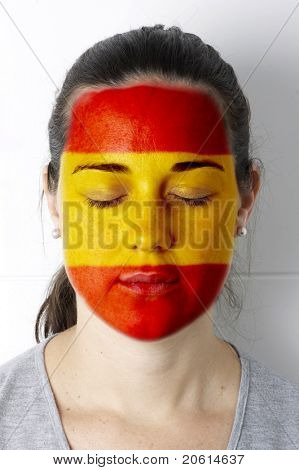 Spanish fan with painted flag on her face.