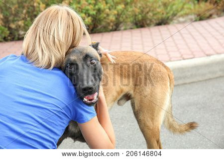 Female volunteer with homeless dog outdoors. Concept of volunteering and animal shelters