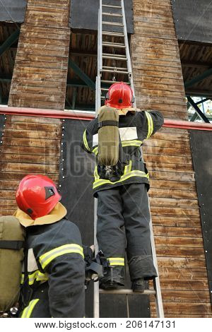 two firefighters in equipment and helmets on test site, one of them climbs assault ladder