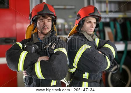 Two firefighters in protective suits with half mask in hand against fire engine, fold ones arms