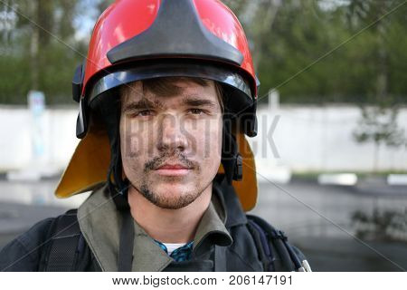 Portrait of fireman wearing fire fighter turnouts and red fire helmet to protect head, closeup