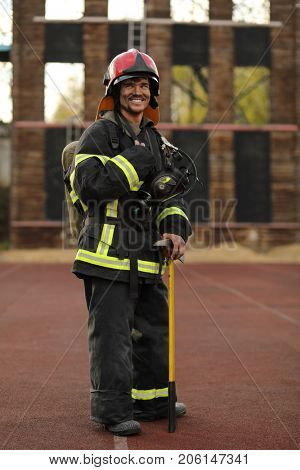 Portrait of smiling fireman wearing fire fighter turnouts, red helmet and breathing apparatus