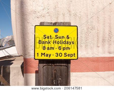 Close Up Orange Parking Sign Outside Sunny Day