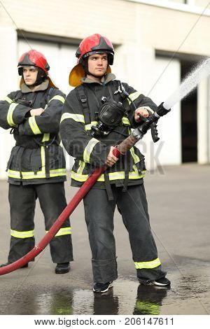 Portrait of two heroic fireman holds and adjust nozzle and fire hose spraying high pressure water