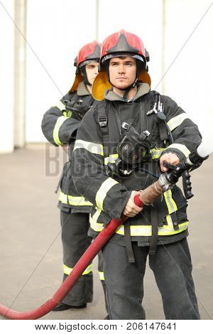 Portrait of two heroic fireman holds and adjust nozzle and fire hose spraying high pressure water, one is behind another poster