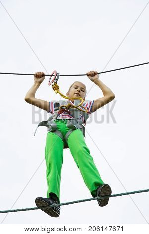 Teenage girl walking on a rope on a rope park