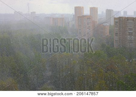 snow in spring in Moscow, landscape of city from window of multi-storey building