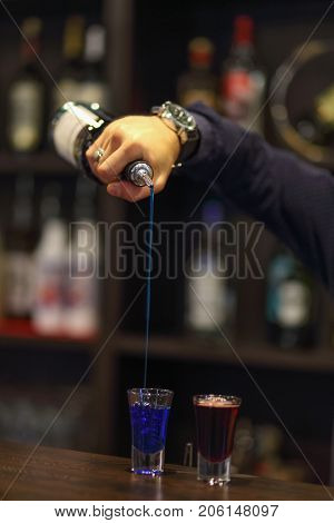 bartenders hands in bar interior making alcohol shot cocktail
