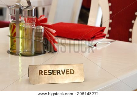 Reserved metal plate with inscription: Reserved on an arranged restaurant white table