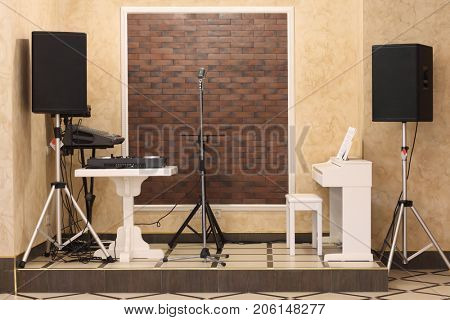 Interior of restaurant with piano, microphone and acoustic system