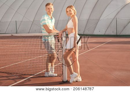 Young couple with tennis rackets standing on court