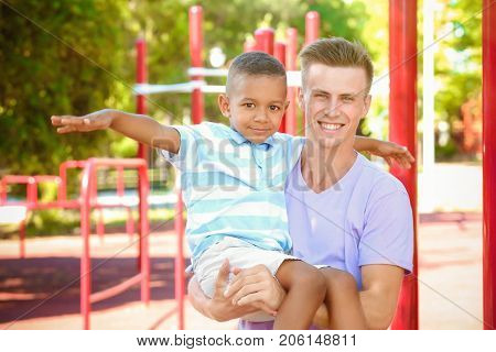 Young father with adopted African American boy outdoors
