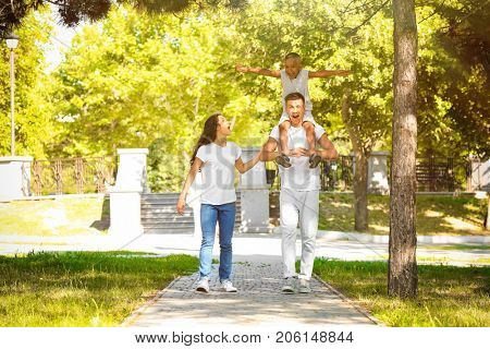 Young family with adopted African American boy in park