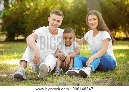Young family with adopted African American boy outdoors