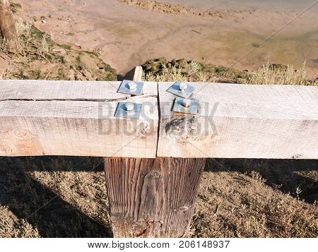 Close Up Of Four Metal Screw Tops On Wooden Fence