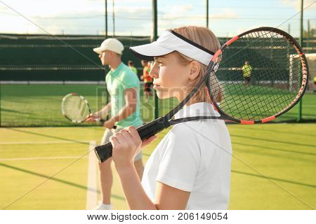 Young couple playing tennis on court