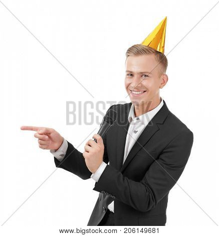 Young presenter in party cap with microphone on white background