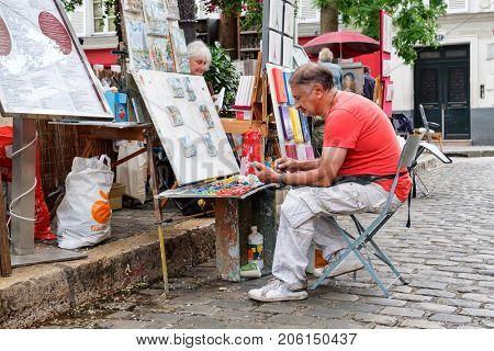 PARIS,FRANCE - JULY 31,2017 : A painter works at the famous Place du Tertre in Montmartre