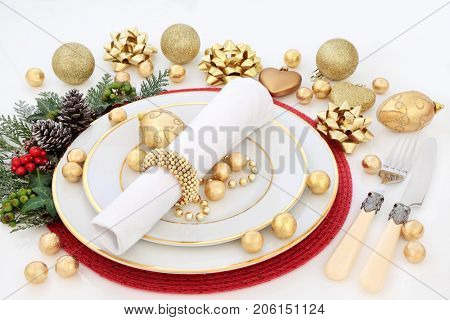 Christmas dinner table setting with porcelain plates, napkin, gold bauble decorations, cutlery, holly, mistletoe, ivy and fir on white background