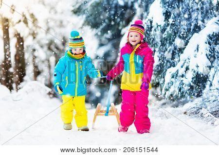 Children Play In Snow On Sleigh In Winter Park