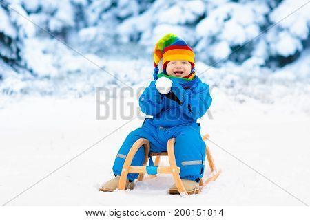Boy On Sleigh Ride. Child Sledding. Kid With Sledge