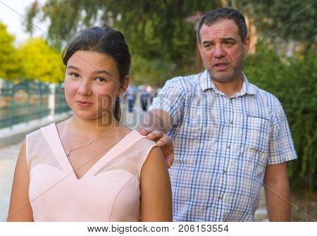 Father comforts his teenager daughter on the street