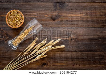 Ingredients for beer. Malting barley in beer glass on wooden background top view. poster