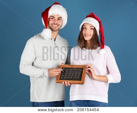 Young couple in Santa hats with chalkboard counting days until Christmas, on color background