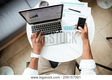 Top view image of young african man sitting coworking with laptop computer chatting by phone.
