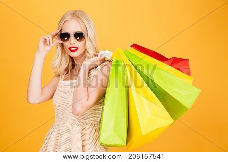 Image of serious amazing young blonde woman standing isolated over yellow wall background. Looking camera holding shopping bags.
