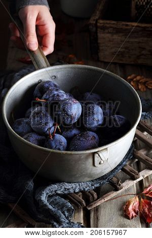 plums with drops of water in a metal ladle