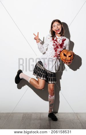 Full length of a happy zombie woman covered in blood stains holding a halloween pumpkin and showing peace gesture isolated over white background