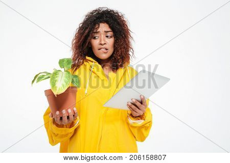 Confused african woman in raincoat holding plant and tablet computer looking at the camera over white background