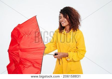 Confused african woman in raincoat close umbrella over white background
